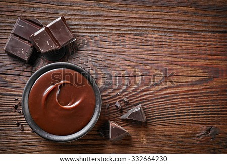 Chocolate cream and chocolate pieces on wooden table, top view - stock photo