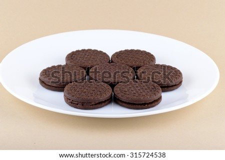 Chocolate cream cookies. brown chocolate sandwich biscuits with cream filling in plate - stock photo