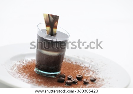 Chocolate cream in taster, chocolate desert on white plate with coffee beans and cocoa powder, patisserie, photography for shop