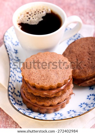 Chocolate cream sandwich biscuits and cup of coffee - stock photo