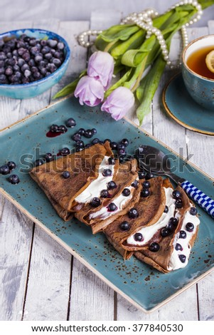 chocolate crepes with cream cheese and blueberries for Breakfast - stock photo