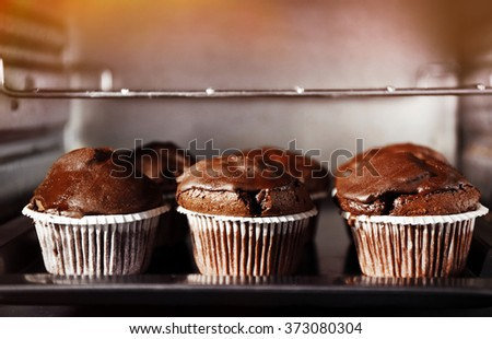 Chocolate cup-cakes in oven, close up - stock photo