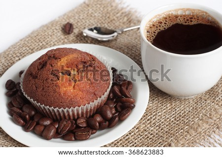 Chocolate cupcake and cup of hot coffee on burlap