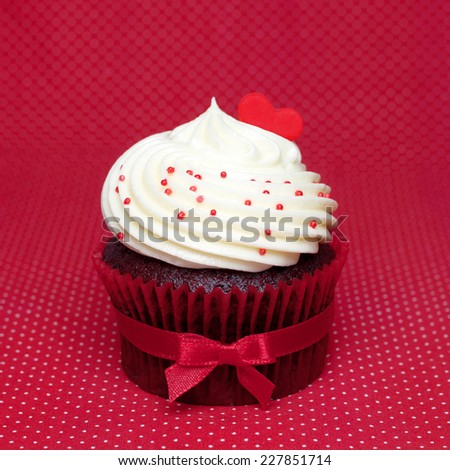 Chocolate cupcake cream white tie red bow ribbon  on a red background. Red hearts for love. - stock photo