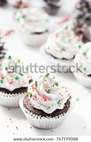 Chocolate cupcake decorated white cream and fir trees. Christmas sweets. New year dessert