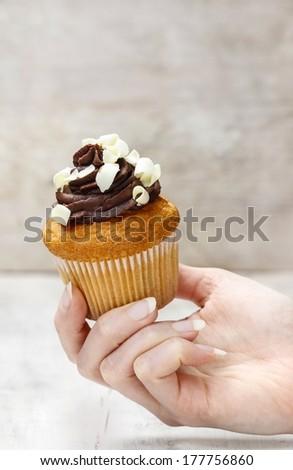 Chocolate cupcake in hand - stock photo