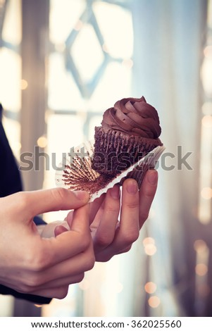 Chocolate cupcake in the hands of baker - stock photo