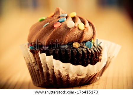 Chocolate Cupcake - This is a shot of a delicious cupcake sitting on a wooden table top. Shot in a warm retro color tone with a shallow depth of field. - stock photo