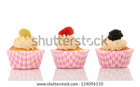 Chocolate cupcake with blue buttercream and fresh bramble berry isolated over white background