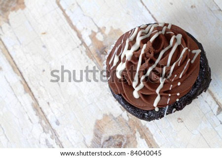 Chocolate cupcake with butter cream icing on grunge wooden background with copy space - stock photo