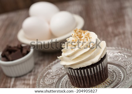 Chocolate cupcake with vanilla frosting with eggs and chocolate pieces