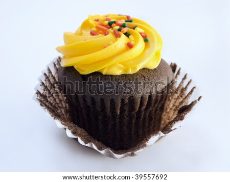chocolate cupcake with yellow icing and sprinkles - stock photo