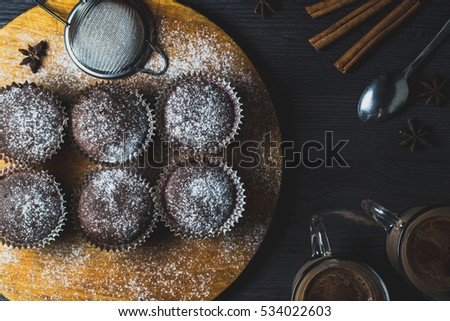 Chocolate cupcakes and cocoa on dark wooden background. Photo in a dark style top view.