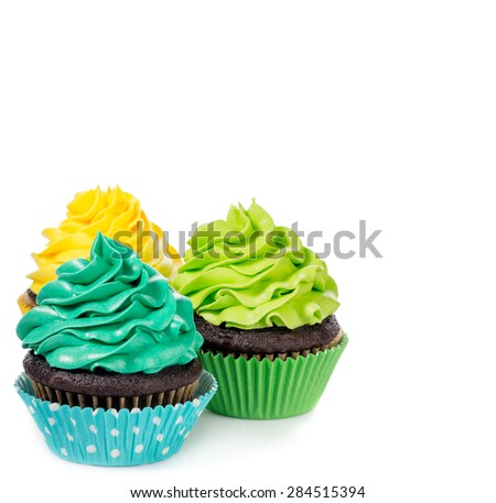 Chocolate cupcakes arranged with colorful icing on a white background.