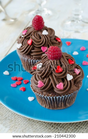 Chocolate cupcakes decorated with sugar hearts and raspberry  - stock photo
