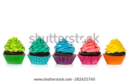 Chocolate cupcakes in a row with colourful icing on a white background.