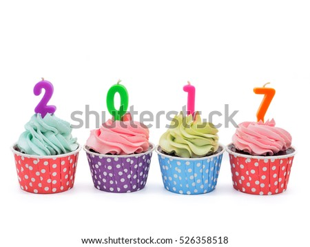 Chocolate cupcakes in rows with candles 2017 on white background (cake, new year, holiday)