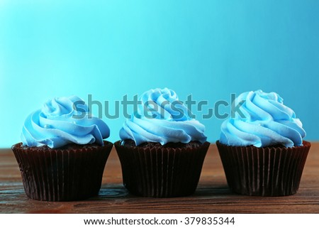 Chocolate cupcakes on wooden table in front of blue background - stock photo