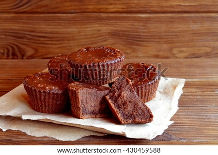 Chocolate cupcakes recipe. Sweet delicious cupcakes made from butter, cocoa, chocolate, sugar, flour, eggs. Oven baked muffins. A lot of chocolate cupcakes on paper and wooden table. Close-up  - stock photo