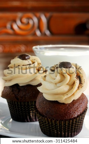 Chocolate cupcakes smothered in mocha frosting topped with roasted coffee bean served with cold glass of milk - stock photo
