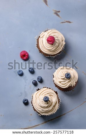 Chocolate cupcakes with butter coffee cream and fresh berries over gray metal surfave. Top view. - stock photo