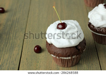Chocolate cupcakes with cherries on a wooden background - stock photo