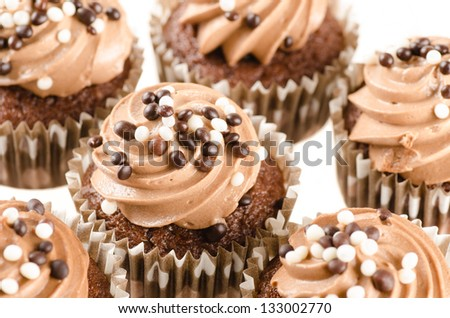 Chocolate cupcakes with chocolate icing and decoration isolated on white - stock photo