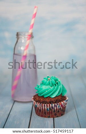 Chocolate cupcakes with peppermint cream stand next to the bottle of lavender lemonade on a blue background