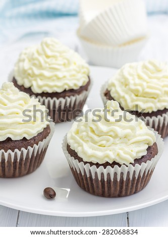 Chocolate cupcakes with ricotta cheese frosting on the white plate - stock photo