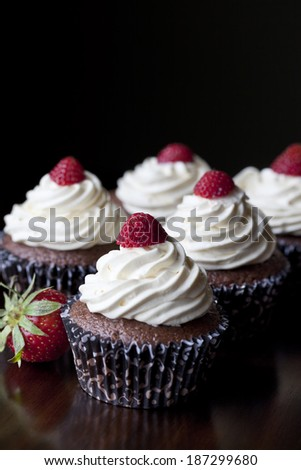 Chocolate cupcakes with vanilla icing topped with strawberries - stock photo