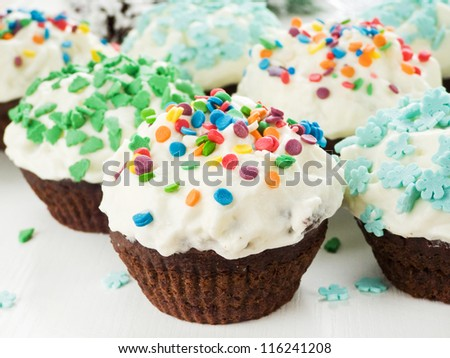 Chocolate cupcakes with whipped cream and colorful sprinkles Shallow dof. - stock photo