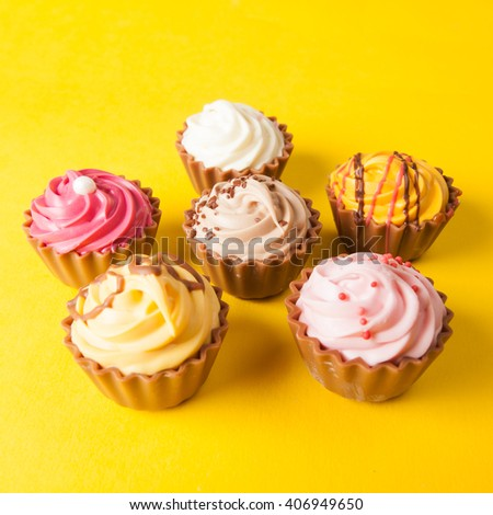 Chocolate cupcakes with yellow backgroud - stock photo