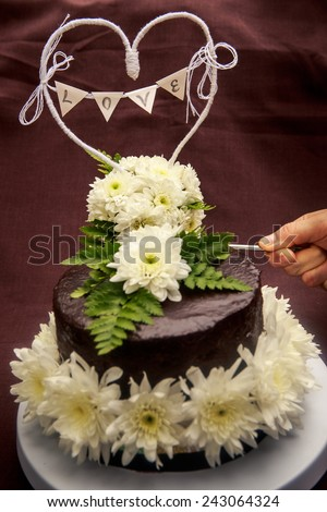 chocolate delicious cake decorated with white flowers and words LOVE
