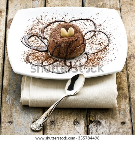 Chocolate dessert cake decorated with chocolate syrup almonds and cocoa powder on white plate next to silver little spoon on wooden rustic table - stock photo