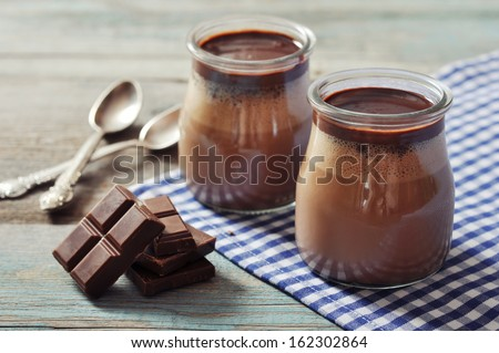Chocolate dessert panna cotta in glass jars on wooden background - stock photo