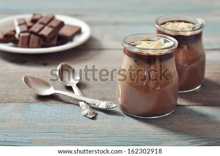 Chocolate dessert panna cotta with almond in glass jars on wooden background - stock photo