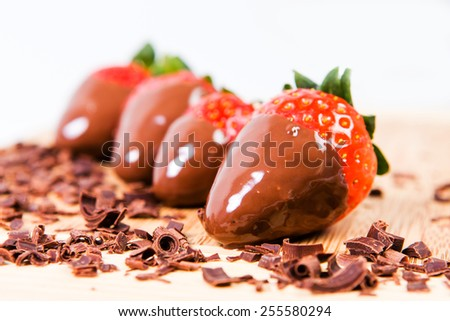 Chocolate dipped strawberries, chocolate pieces around him. - stock photo