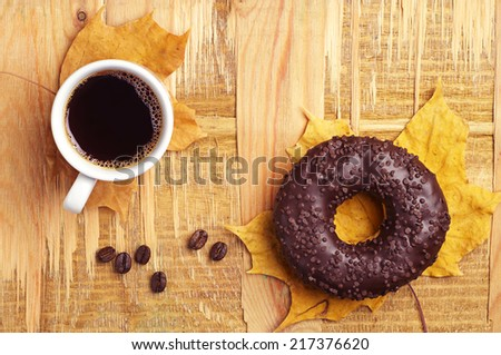 Chocolate donut, cup of hot coffee and autumn leaves on wooden background. Top view