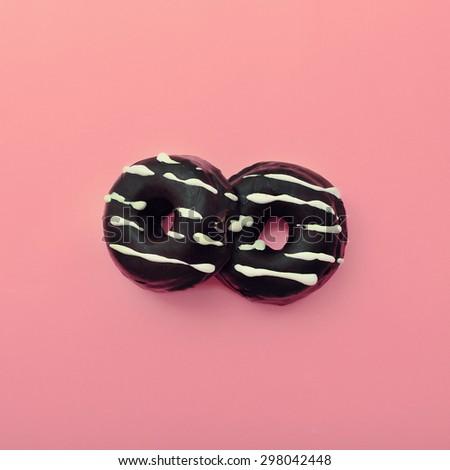 Chocolate Donuts on pink Vanilla background - stock photo