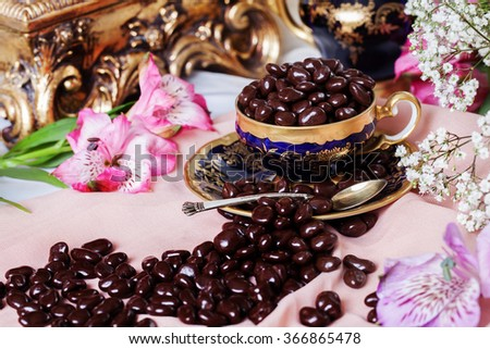 chocolate dragees in a porcelain coffee cup, elegant still life with baroque stucco, luxury, dating, love, - stock photo