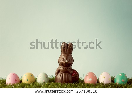 Chocolate easter bunny and vintage hand painted easter eggs over grass - stock photo
