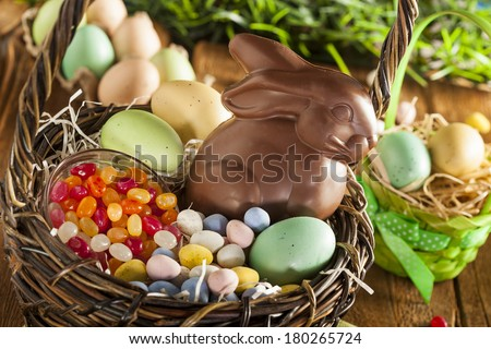 Chocolate Easter Bunny in a Basket with Assorted Candy - stock photo