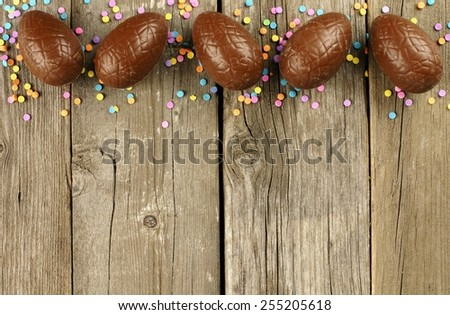 Chocolate Easter egg top border over a wood background - stock photo