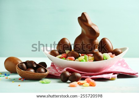 Chocolate Easter eggs and rabbit on plate, on color wooden background - stock photo