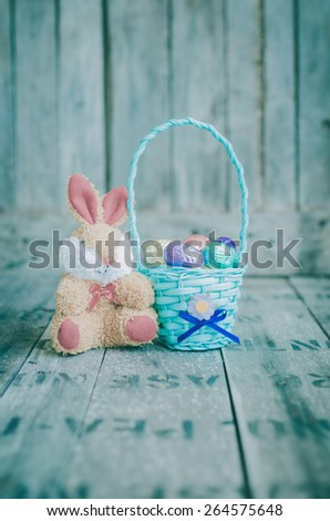 chocolate easter eggs in a basket and rabbit doll on wooden background.  Vintage toned - stock photo