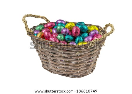 chocolate easter eggs wrapped in colorful aluminum foil in a basket isolated on white background
