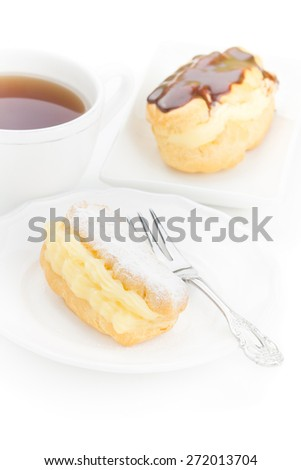 Chocolate eclair dessert powdered sugar filled custard on a white plate with an elegant fork and cup of tea - stock photo