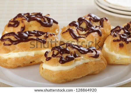 Chocolate eclairs with cream filling on a platter