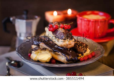 Chocolate eclairs with custard cream and cup of coffee on cozy candles evening background - stock photo