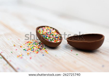 Chocolate egg with colorful little sprinkles on white wooden surface. High angle view, horizontal, copy space, no retouch, shallow depth of field. - stock photo